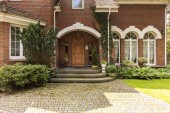Fotografie Cobbled path and steps leading to a stylish entryway with ornamented wooden door and side windows in a red brick English style mansion.