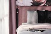 Reggeli tálca szürke ágyon fekete párna rózsaszín hálószoba belső a drapéria. Valódi fotó összpontosítva a tálca