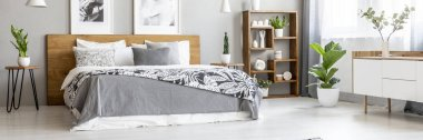 Scandinavian style, wooden furniture in a stylish, monochromatic bedroom interior with plants, gray walls and industrial elements