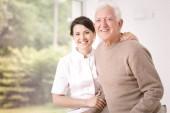 Badante sorridente amichevole che abbraccia felice uomo anziano in ospedale
