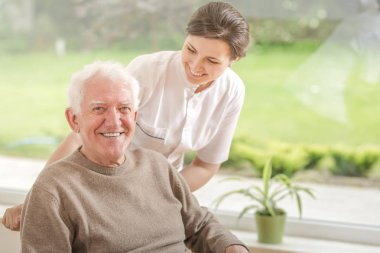 Happy caregiver helping smiling elderly man in the nursing house