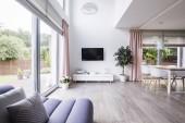 Fotografie Prostorný obývací pokoj interiér s oříznutého sedačka, Tv, skříň, okno, rostlin a jídelní stůl s židlemi. Reálné Foto