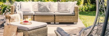 Panorama of rattan sofa with pillows and table on terrace in the garden. Real photo