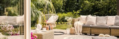 Panorama of rattan couch with cushions and hanging chair on terrace during spring. Real photo