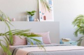 Photo Real photo of bright bedroom interior with decor, double bed with pastel sheets, books on bedside table and modern art painting