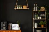 Reálné fotografie interiéru moderní kuchyni s policemi, rostliny, kávovar a sklenice na víno na černou zeď
