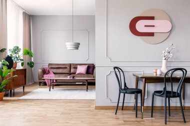 Real photo of open space living room interior with modern clock on wall with molding, table with black chairs and leather sofa in the background