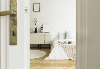 A peek through a half open door into a monochromatic beige and white bedroom interior with a bed and a drawer cabinet. Real photo.