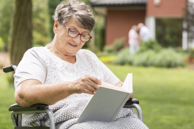 An elderly woman in a wheelchair reading a book during summer day outside in the garden of a care home for seniors. Blurred background.