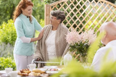 A tender caretaker assisting an elderly woman with a walker during an afternoon snack time on a patio in the garden of a private nursing home.