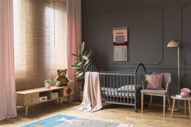 Plush toy on wooden cupboard next to grey cradle in child's pastel bedroom interior. Real photo