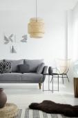 Lampe über grauer Couch mit Kissen im weißen Wohnzimmer-Interieur mit Sessel und Postern. Echtes Foto