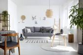 Fotografie Holzstuhl am Tisch in weißem Wohnzimmerinterieur mit grauem Sofa an der Wand mit Postern. echtes Foto
