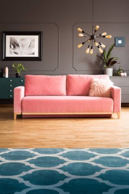 Real photo of powder pink sofa with fur cushion standing in dark sitting room interior with modern lamp, molding on wall and carpet with moroccan trellis