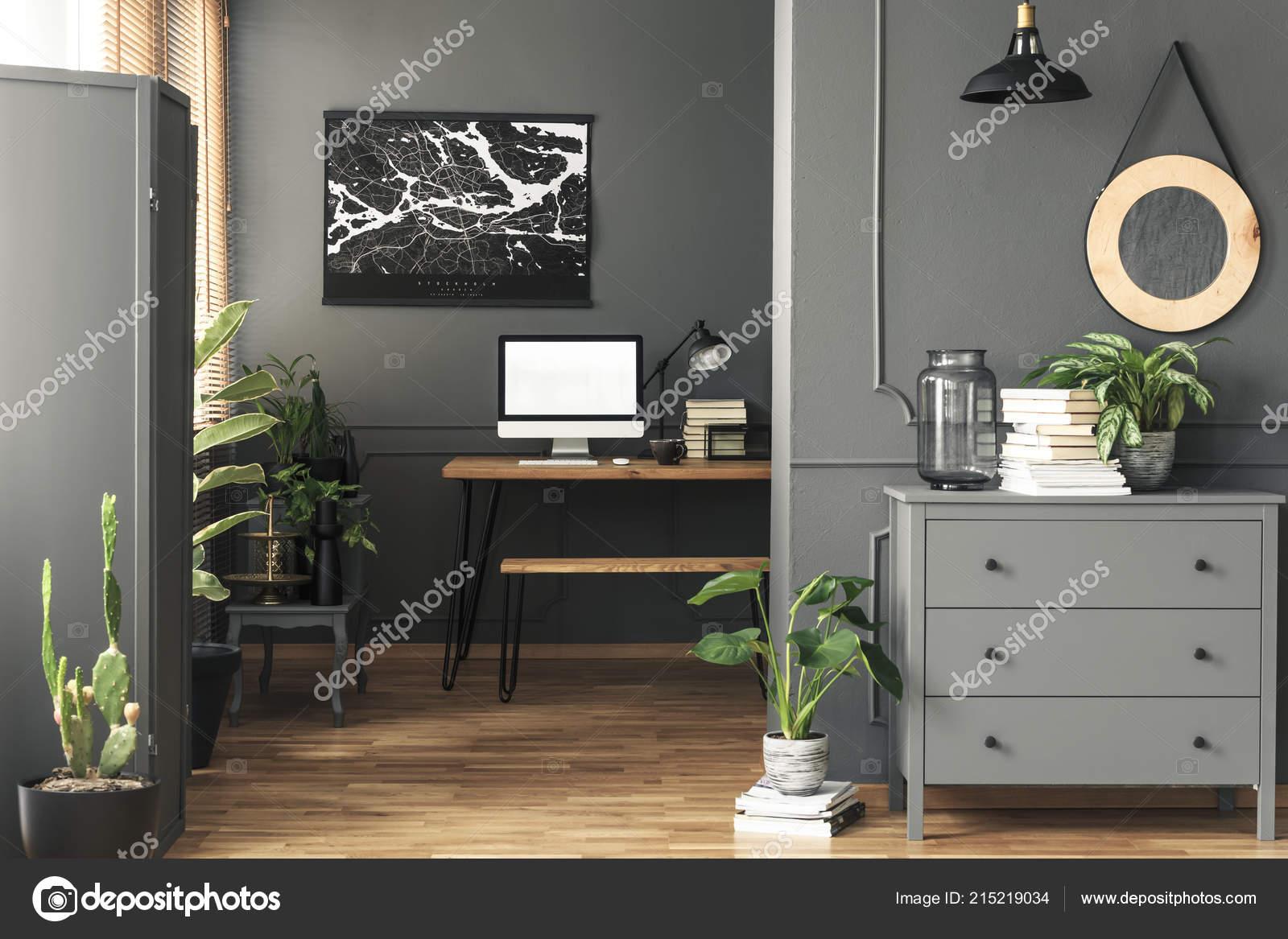 Affiche noir sur mur gris dessus bureau avec maquette intérieur