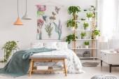 Blízko k přírodě interiér světlé ložnice s postelí pokryté bílými listy a mořské deku. Zelené rostliny na policích k posteli. Reálné Foto