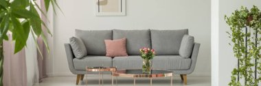 Real photo of grey settee with dirty pink pillow standing in white living room interior with fresh plant and roses in glass vase placed on metal table