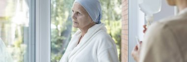 Panorama of weak elderly woman with cancer during chemotherapy
