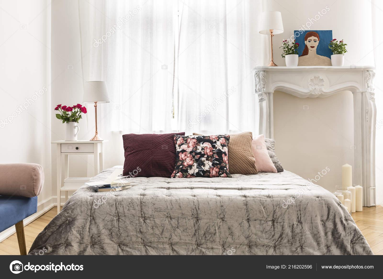 Interno camera letto elegante dotata letto con cuscini multicolore
