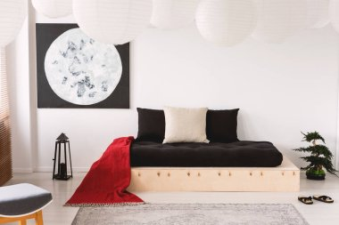 Black sheets and red blanket on wooden bed in bedroom interior with moon poster. Real photo