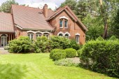 Real photo of garden with bushes and beautiful brick house