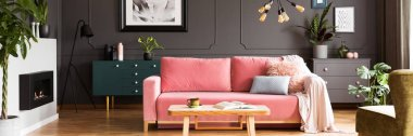 Wooden table in front of pink sofa with blanket in grey living room interior with fireplace. Real photo