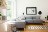 Fotografie Black and white textiles and decorations in a classic scandinavian style living room interior with wooden furniture and natural sunlight