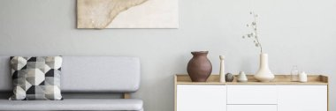 Graphic, pillow on a gray sofa and a white, wooden cabinet with vases in a monochromatic living room interior with natural decorations