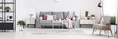 Real photo of white living room interior with grey sofa with cushions, fresh plants and cupboards with decor