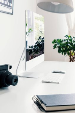 Notebook, camera and desktop computer on white desk in workspace interior with plant. Real photo