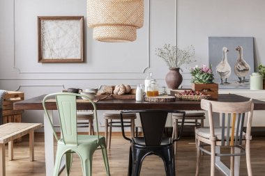 Colorful chairs at wooden table in grey dining room interior with posters and flowers. Real photo