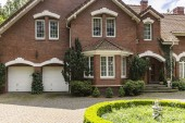 Fotografie Real photo of a brick house with a bay window, garages and round garden in front of the entrance