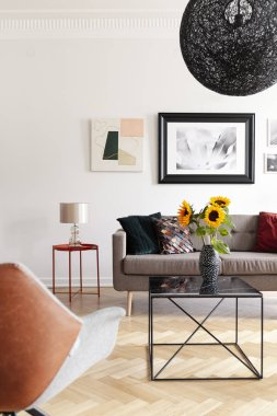 Sunflowers on table in modern living room interior with lamp and posters above sofa. Real photo