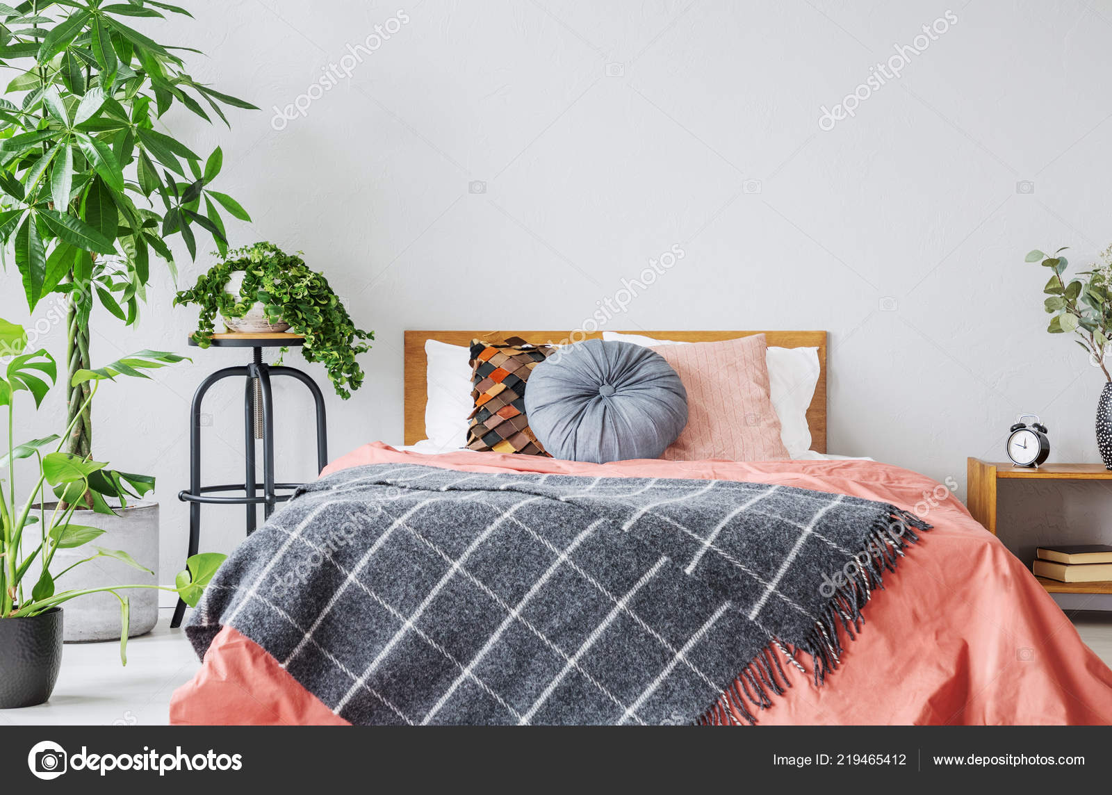 Patterned blanket red bed cushions grey bedroom interior plants real stock photo