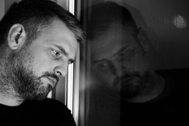 Black and grey photo of depressed and lonely man with alcoholism problem