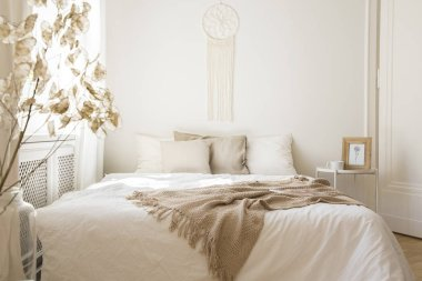 Blanket on white bed with cushions in minimal bedroom interior with plant and table. Real photo