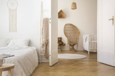 White apartment interior with herringbone parquet, double bed and open door to kid room with peacock chair, white crib and round rug on the floor