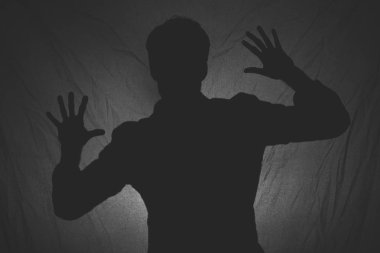 Black and white photo of shadow of a man behind the dark fabric
