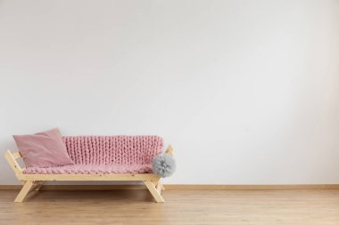 Wooden settee covered with pink blanket and with pink pillow on it in empty living room with white walls and wooden floor
