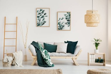 Stylish bright living room with moss green accents, real photo