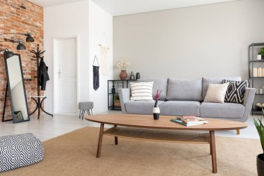 Round wooden table in the middle of elegant living room with grey sofa, metal shelf and mirror, real photo with copy space on the wall