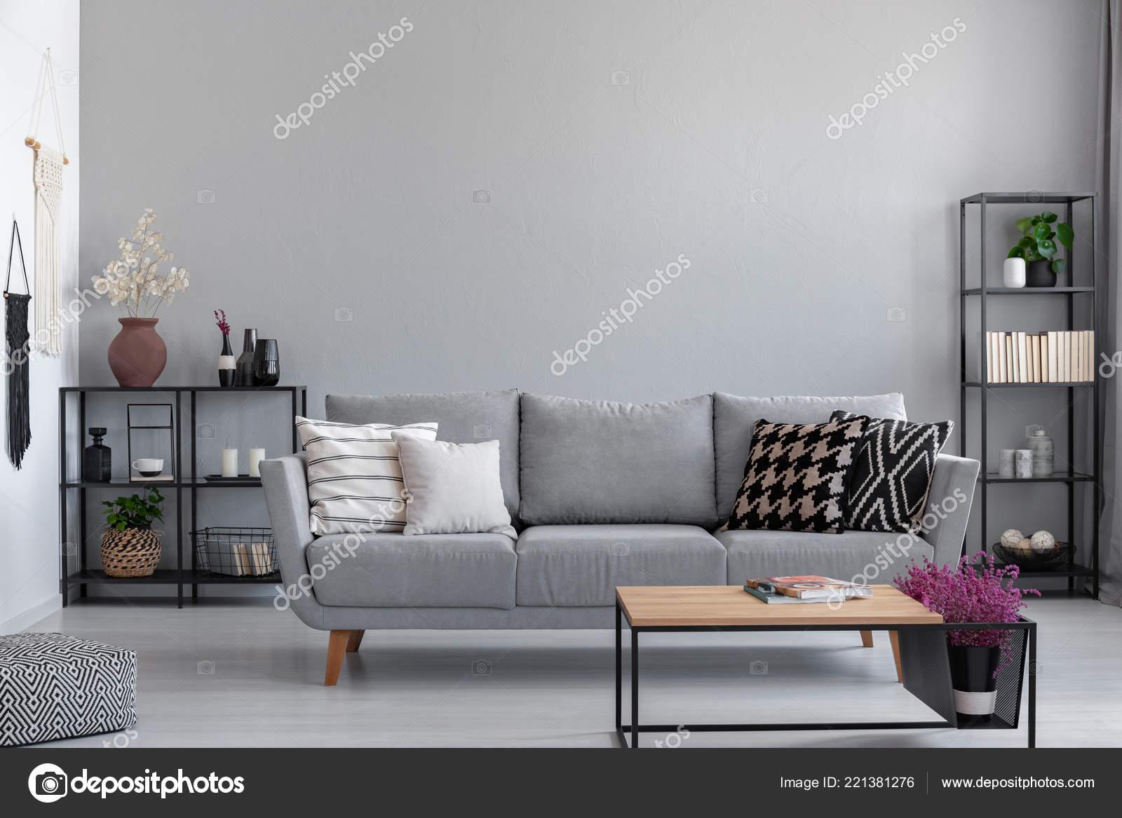 Parete Dietro Divano Grigio : Ripiani metallo neri con libri candele piante dietro divano grigio