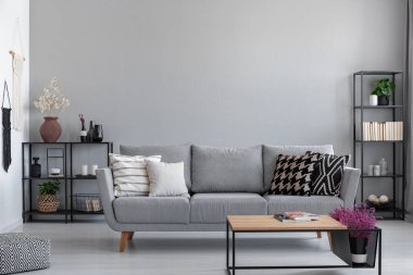 Metal black shelves with books, candles and plants behind the grey sofa with patterned pillows, real photo with copy space on the wall