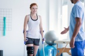 Fotografie Woman walking with crutches during physiotherapy