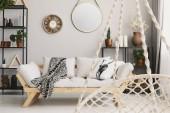 Fotografie Unscharfer Hängesessel im Vordergrund und Holzsofa im Wohnzimmerinnenraum mit Spiegel. echtes Foto