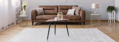 Panoramic view of stylish interior design idea with brown leather sofa and small tables, real photo