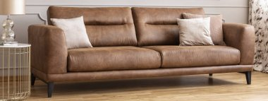 Panoramic view of big comfortable leather sofa with pillows, real photo