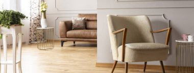 Panoramic view of retro armchair in elegant living room with brown leather sofa, real photo