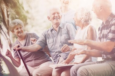 Smiling senior man with walking stick relaxing with elderly woman and friends