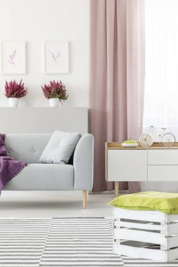 Real photo of white living room interior with couch with pillow, fresh heathers, posters on wall, dirty pink curtain and handmade crate pouf placed on carpet